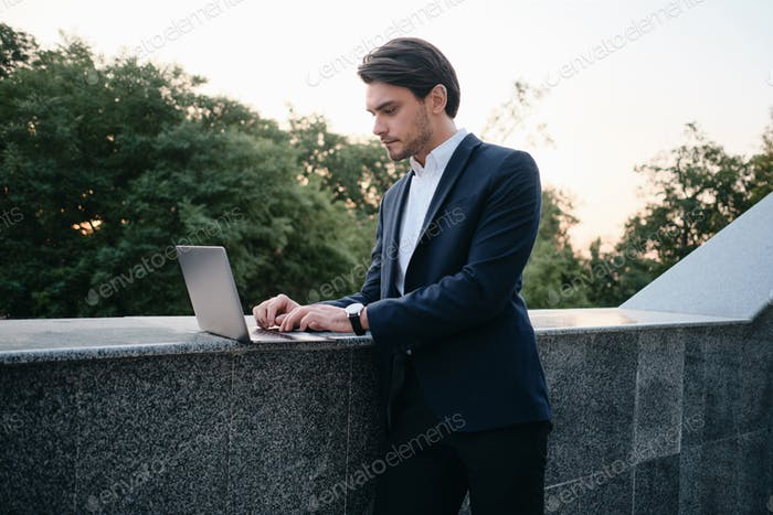 Young attractive brunette man in classic suit standing on street and thoughtfully working on laptop