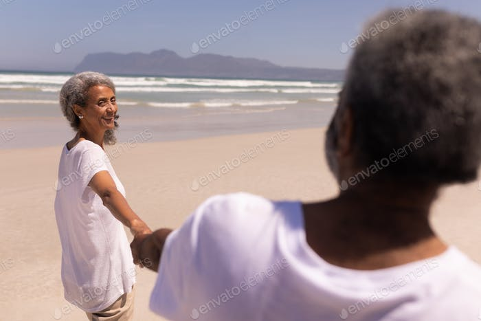 Happy senior couple holding hands on beach in the sunshine with mountains in the background