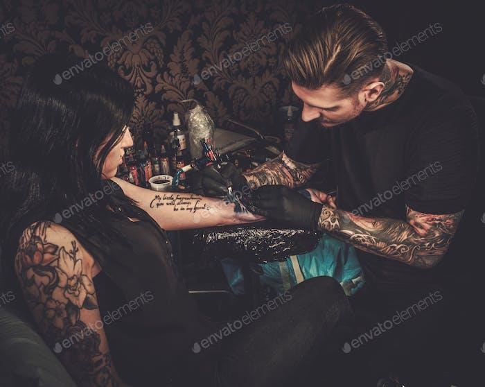 Tatuador profesional hace un tatuaje en la Mano de una niña.