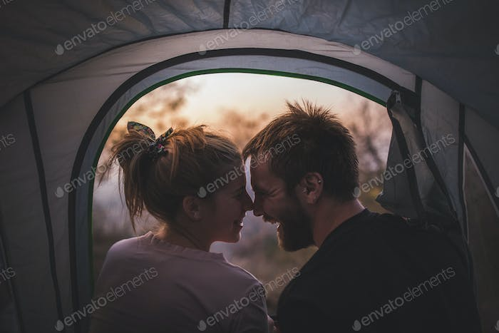 Young happy couple relaxing on camping in autumn day at the forest.