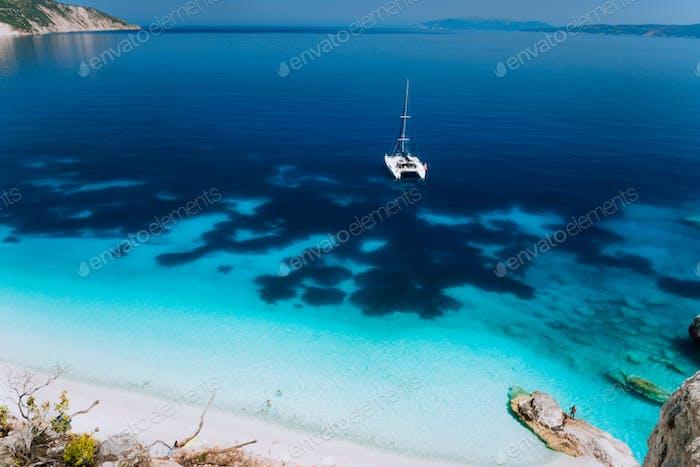 Weiße Katamaran-Yacht Drift auf klarem azurblauen Wasseroberfläche in ruhiger, blauer Lagune mit transparentem Wasser