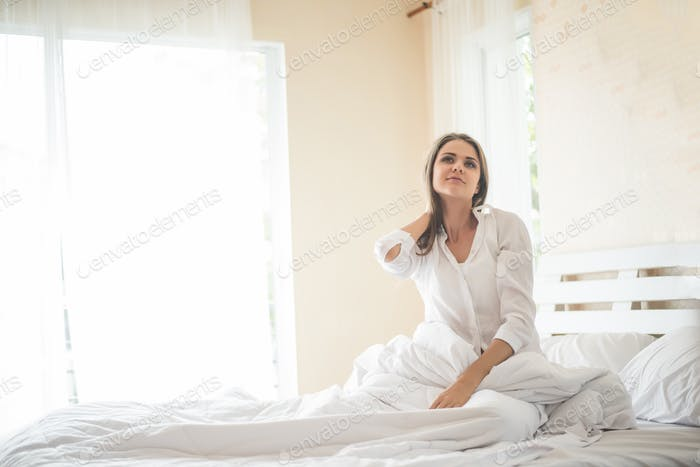 Lazy young woman sitting in bedroom