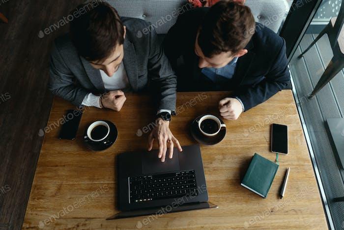 Dos jóvenes empresarios que tienen una reunión exitosa en el restaurante.