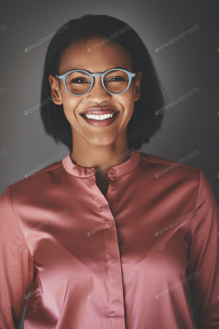 Confident young African businesswoman smiling against a gray background