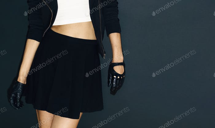 Glamorous lady in stylish leather gloves on black background roc