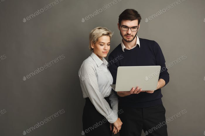 Couple with laptop on grey background