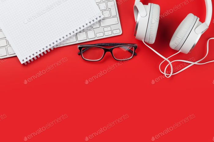 Büro-roter Arbeitsplatz mit Kopfhörern, Zubehör und Computer