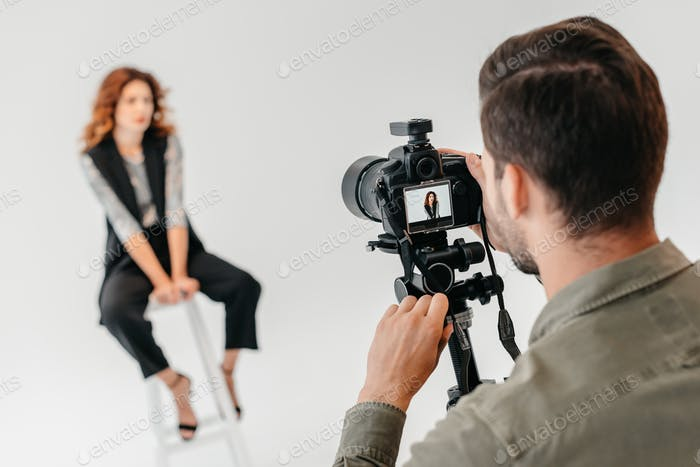 professional photographer and beautiful model on fashion shoot in photo studio with lighting