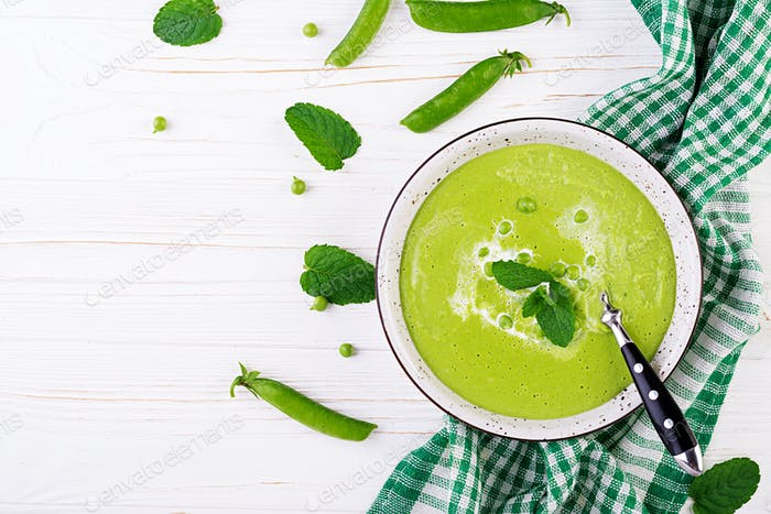 Green pea soup in bowl on wooden table. French cuisine. Top view