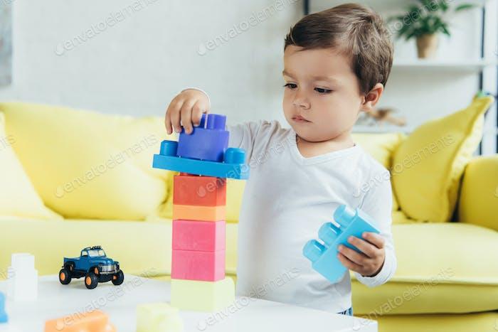 niño adorable jugando con bloques constructores y juguetes en casa