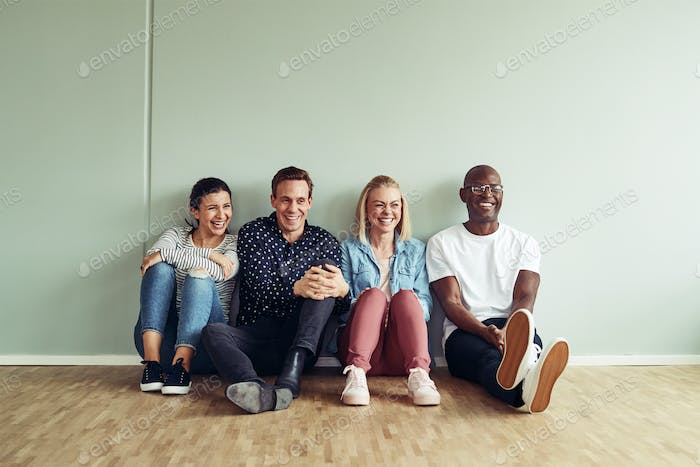Diverse businesspeople laughing together while sitting on an office floor