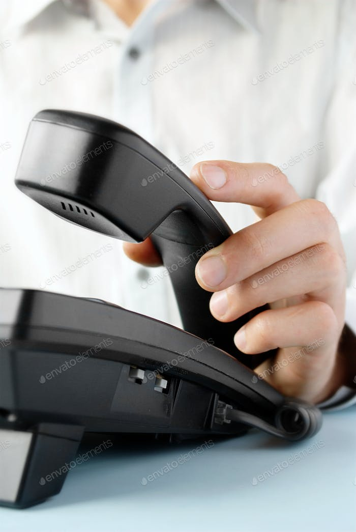 in the office of a man holding up the phone