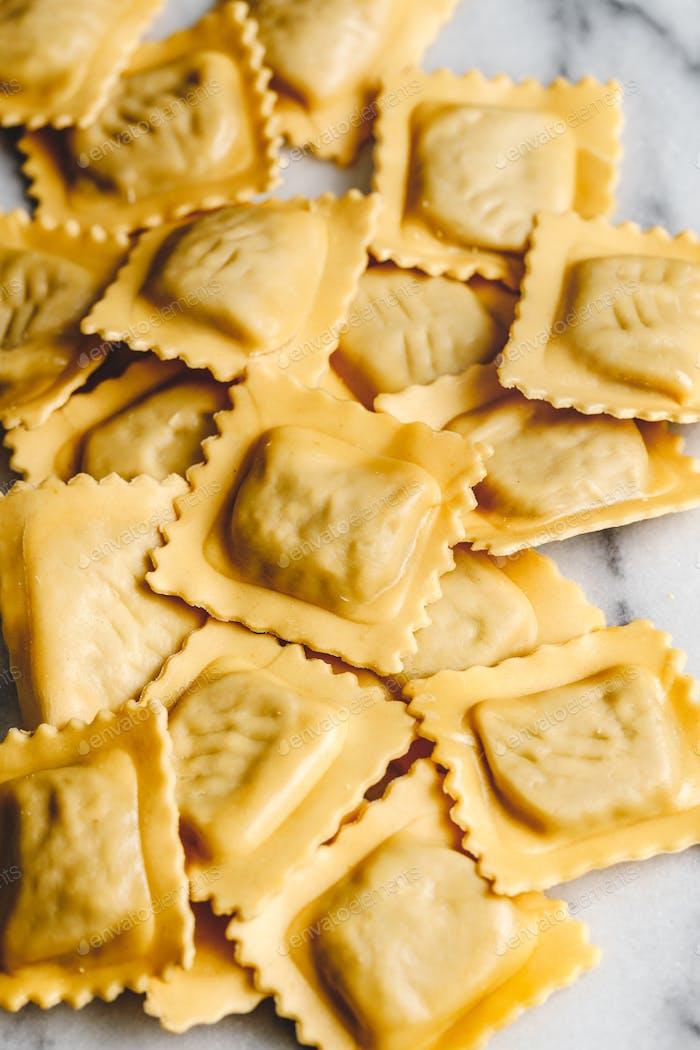 Blick von oben auf hausgemachte rohe italienische Ravioli Pasta auf weißem Hintergrund.