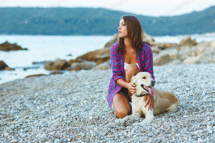 Woman with a dog on a walk on the beach