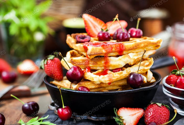 Belgian waffles with fresh berries and jam for breakfast