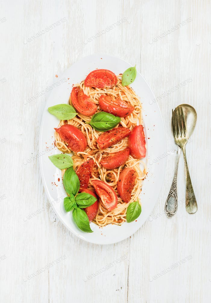 Pasta with roasted tomatoes and basil over white wooden background