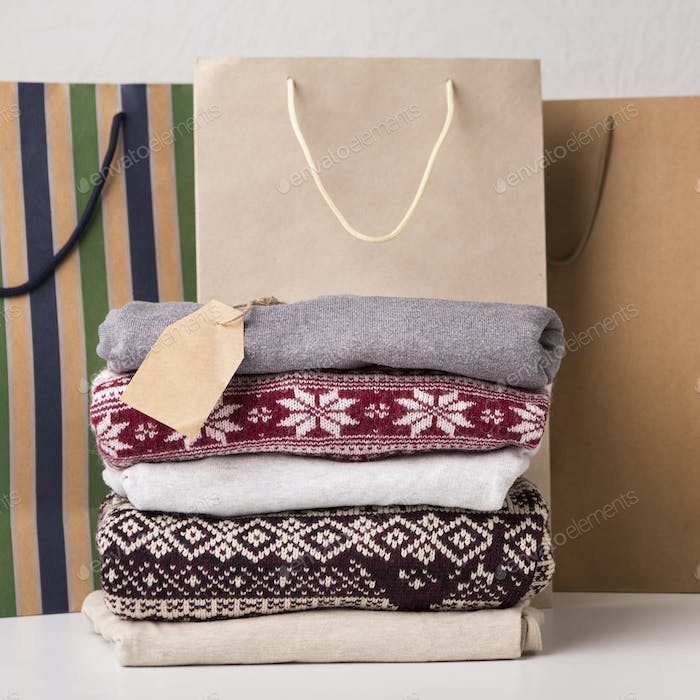 Woolen sweater with patterns and shopping bags on table