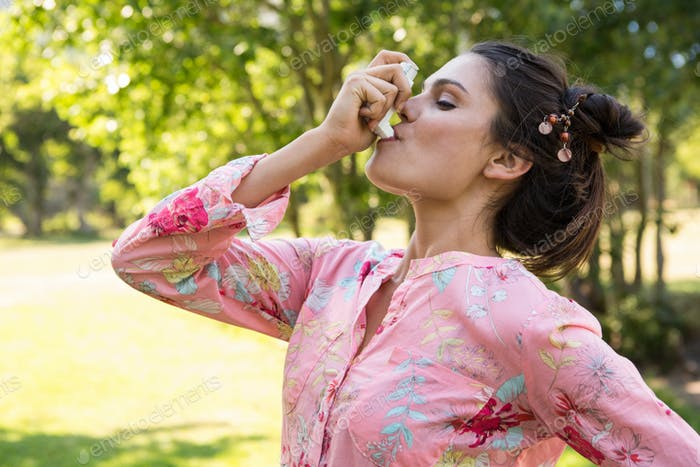 Pretty brunette using her inhaler on a summers day