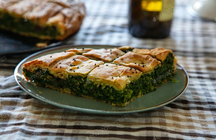 Spinach pie or greek spanakopita serving on kitchen table