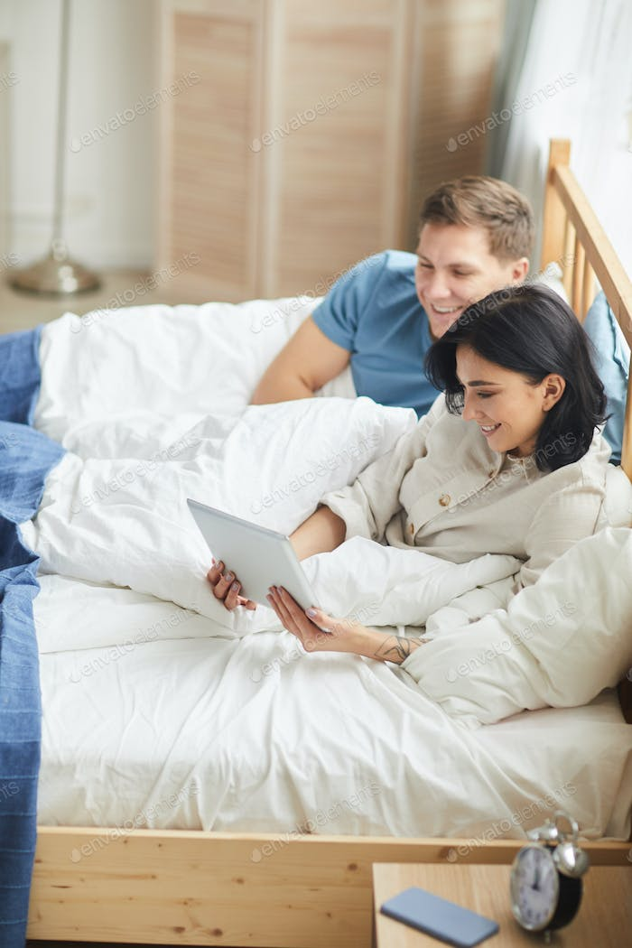 Happy Young Couple Using Tablet in Bed