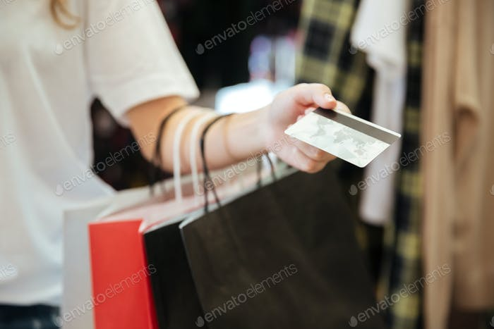 Cropped photo of lady with shopping bags holding debit card.