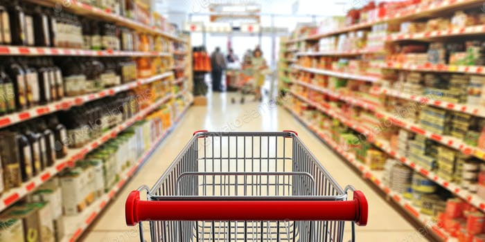 Shopping trolley, empty, with red handle on blur supermarket aisle background. 3d illustration