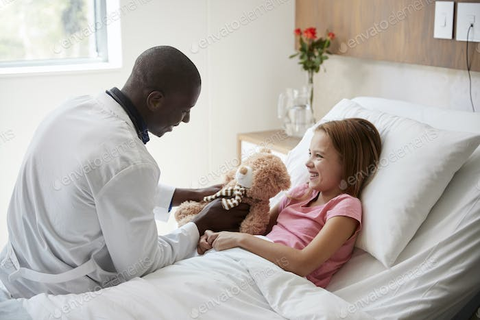Male Doctor Visiting Girl Lying In Hospital Bed Hugging Teddy Bear