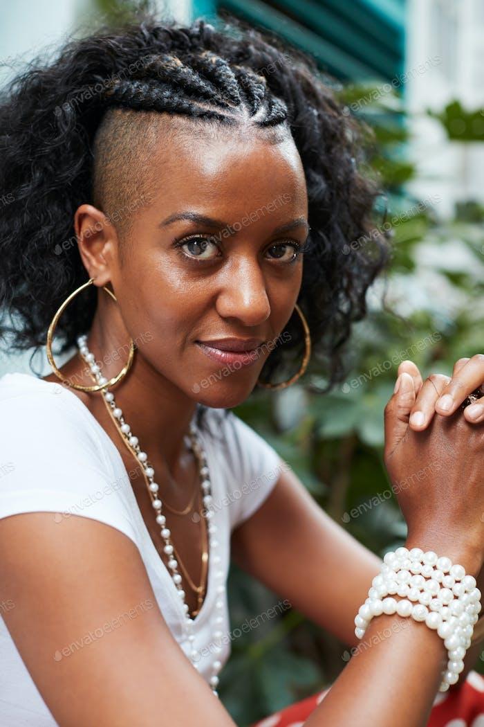 Junge schwarze Frau sitzt im freien Blick auf die Kamera, vertikal