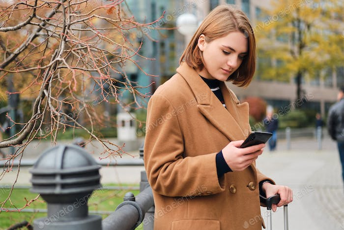 Attractive stylish girl thoughtfully using cellphone on street