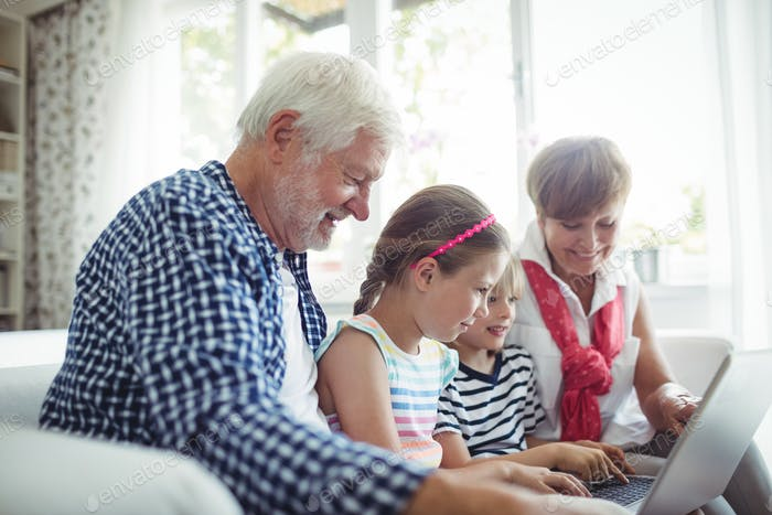 Enkelkinder mit Laptop mit ihren Großeltern
