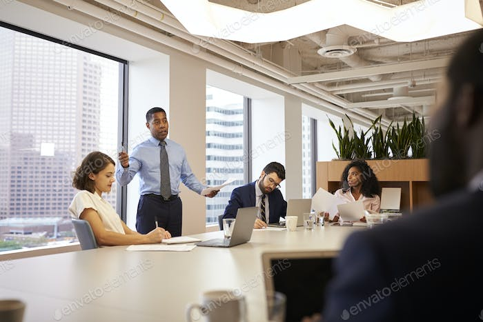 Mature Businessman Standing Giving Presentation To Colleagues In Modern Open Plan Office