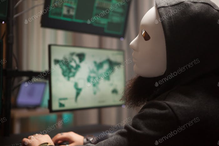 Bearded hacker with a hoodie wearing a white mask