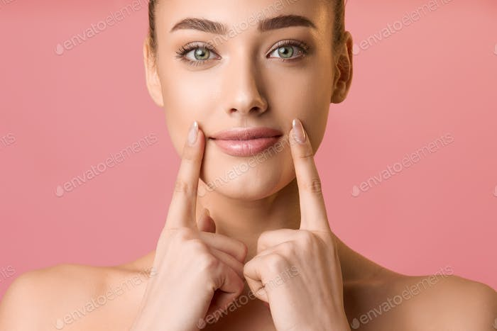 Natural beauty. Young woman applying lip balm