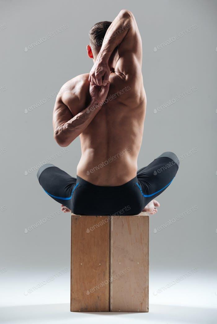 Man sitting on wooden box and stretching hand