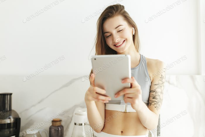 Beautiful smiling lady in sporty top standing with laptop in hand and earphones