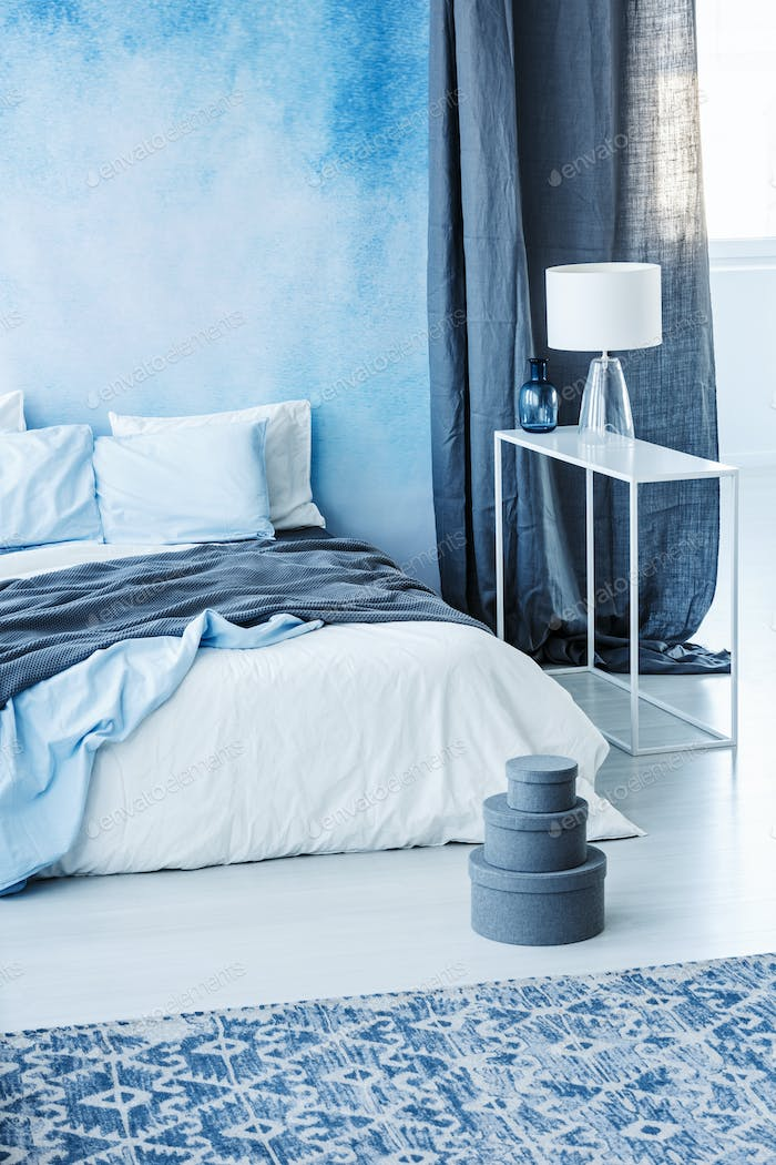 Thumbnail for Patterned carpet and grey boxes next to bed with blue bedding in