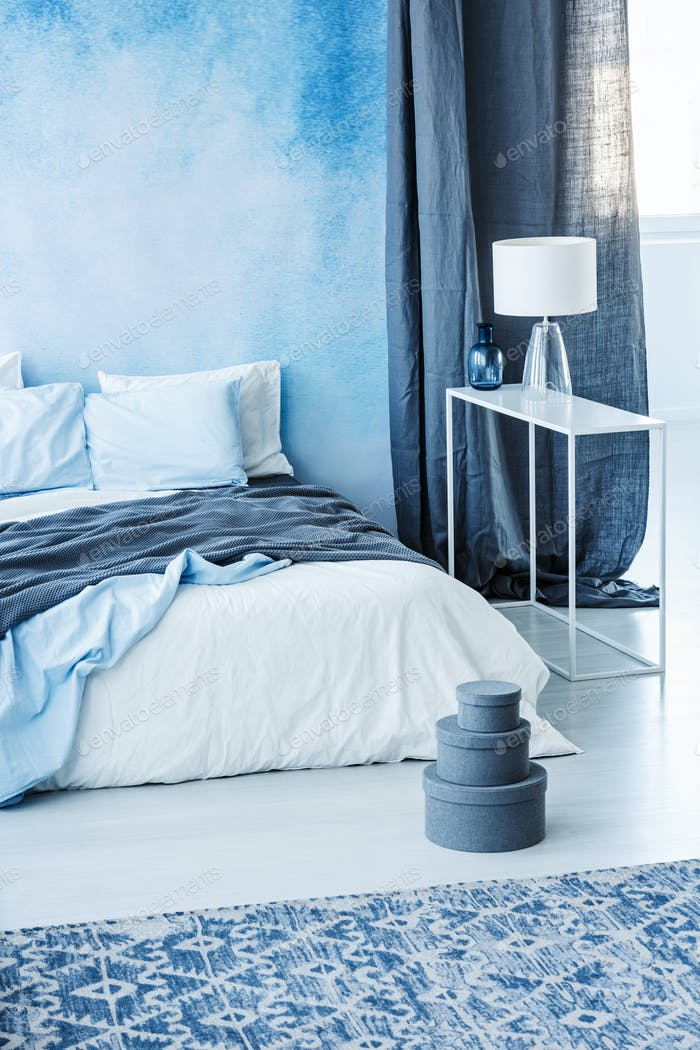 Patterned carpet and grey boxes next to bed with blue bedding in