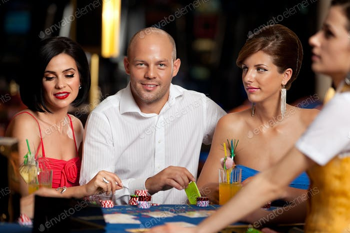 handsome blackjack player with two elegant women