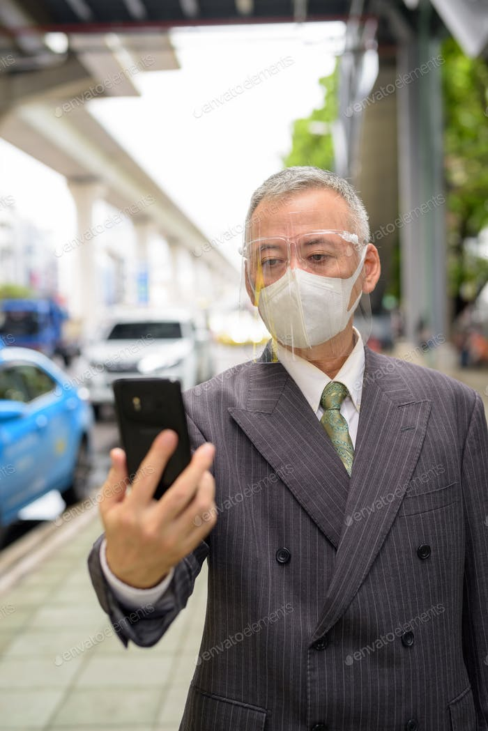 Mature Japanese businessman with mask and face shield using phone at the taxi station