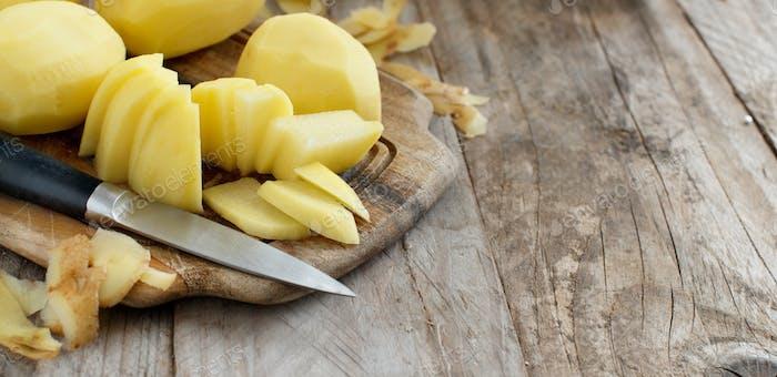 Rohe geschälte Kartoffeln mit einem Messer