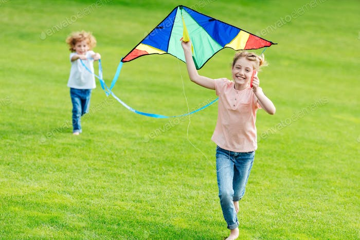 happy cute siblings playing with kite while running on green lawn in park