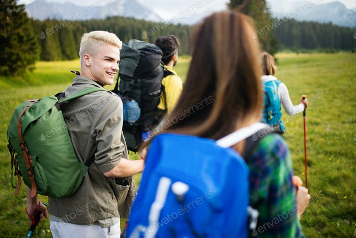 Young friends on a country walk. Group of people hiking through countryside