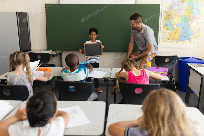 Happy schoolboy holding slate board and standing at greenboard in classroom