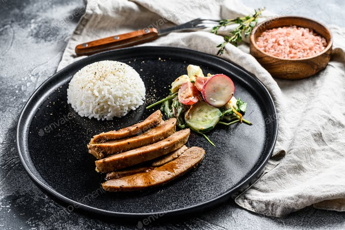 Turkey breast steak, poultry, side dish of rice and salad. Gray background. Top view