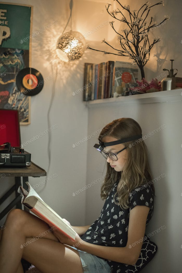 A girl reading a book in a quiet corner using a head torch.