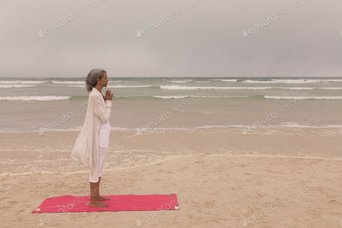 Side view of senior woman with eyes closed and hands clasped doing yoga on the beach