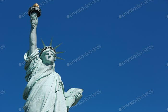 Statue of Liberty in a sunny day, blank blue sky space