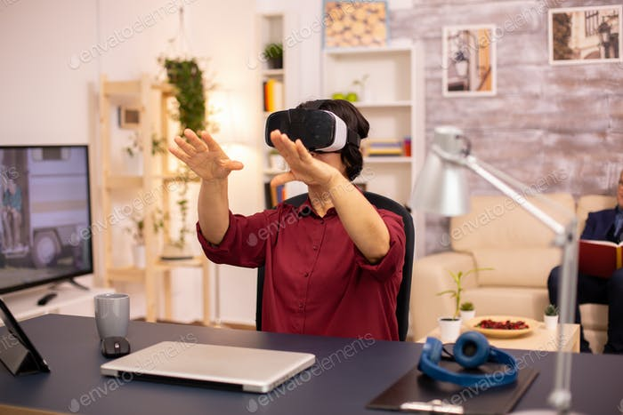 Old elderly woman using a VR virtual reality headset for the first time