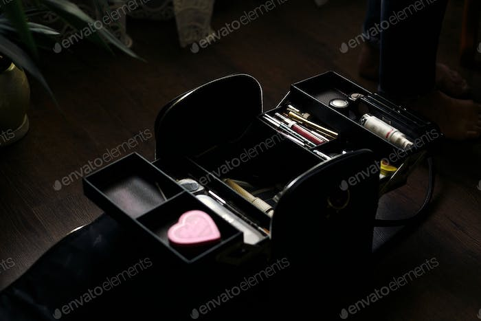 beautician bag full of make up cosmetics. cosmetician case on wooden table
