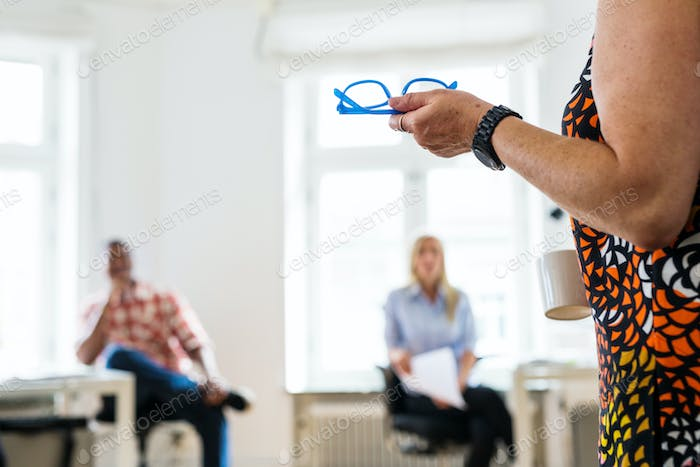Woman holding eyeglasses during business meeting in office